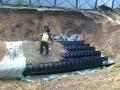 Pracownicy zasypujący rury w wykopie